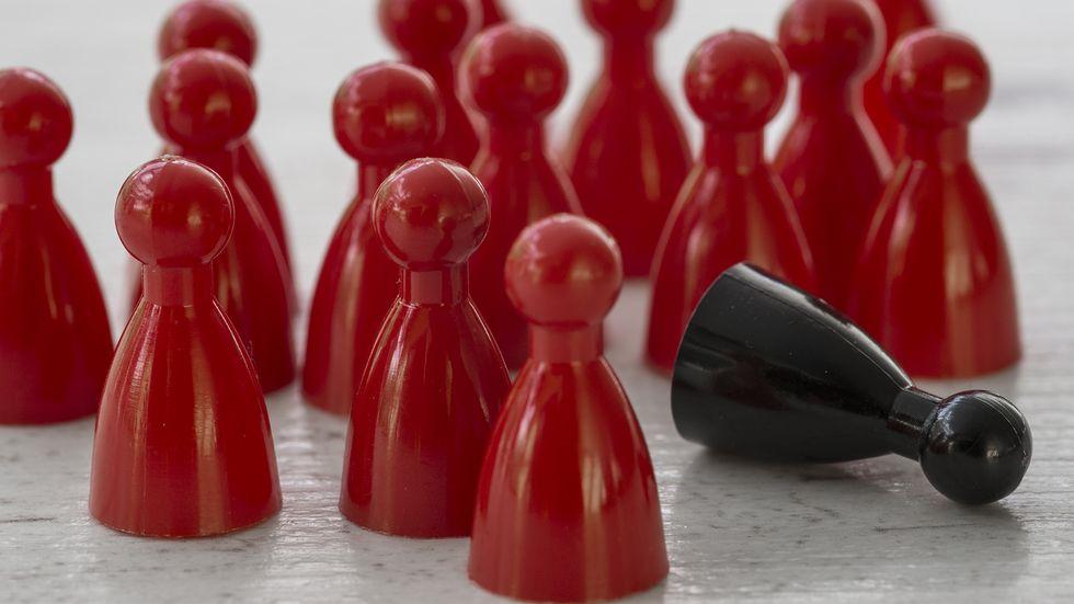 Spielfiguren; alle rot, eine schwarz, die schwarze ist umgekippt