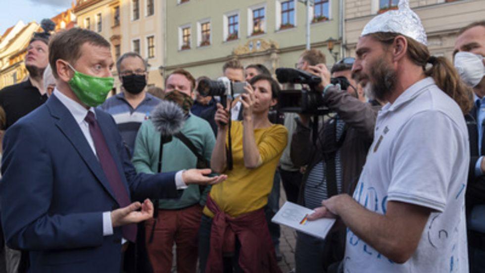 Ministerpräsident Michael Kretschmer spricht mit einem Gegner der Corona-Maßnahmen. Unter Kontrolle der Polizei demonstrieren Gegner wie Befürworter der aktuellen Regelungen im Zusammenhang mit der Bewältigung der Corona-Pandemie. Foto: Matthias Rietschel/dpa-Zentralbild