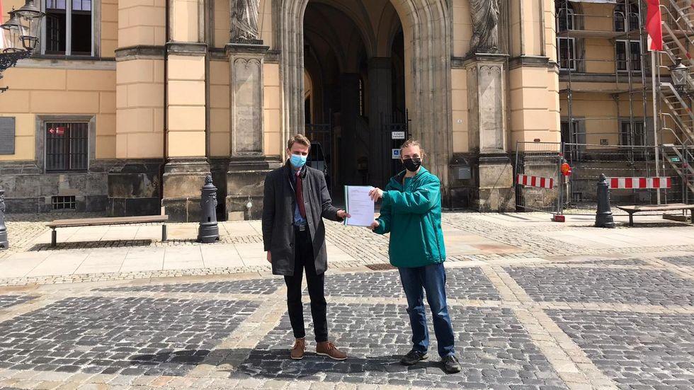 Jay-Cee Watzke (links) und Alexander Hilse mit dem Bürgerbegehren vor dem Zittauer Rathaus.